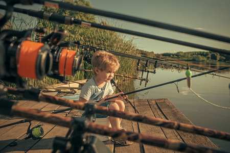 child is fishing. Summer vacation of little boy fishing on river. Imagens