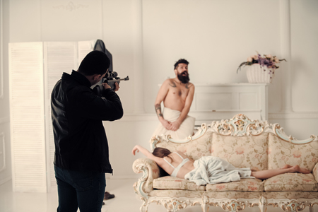 Cheating husband. Cheating and jealousy concept. Man with beard naked, scared, shocked at gunpoint, interior background. Husband found lovers, killed wife and threatening to bearded lover. Stockfoto
