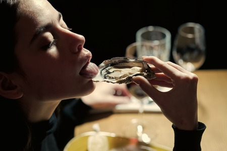 Elegant life. Dieting and health. Seafood and Mediterranean cuisine with mussels in shell. Woman eating shellfish. Young woman eating oyster in luxury restaurant. delicacy with omega 3 vitamin. Фото со стока