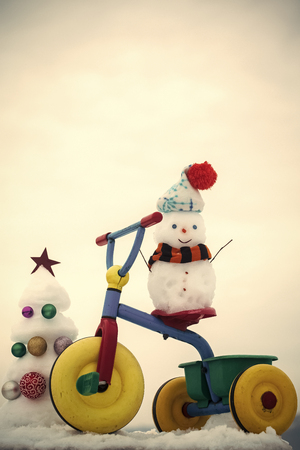 Merry Christmas. Snowman riding tricycle on white sky. Snow sculptures and xmas tree on snowy background. Christmas and new year celebration. Winter holidays concept. Stock Photo