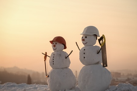 snowmen builders. christmas snowman builders in helmet with saw in winter outdoor Stock Photo