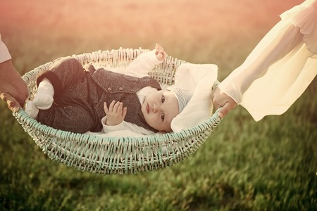 Child custody. Infant son lie in basket held in hands on green grass. Vacation, wanderlust, travel concept. Comfort, relax, tranquility. Family, love support protection