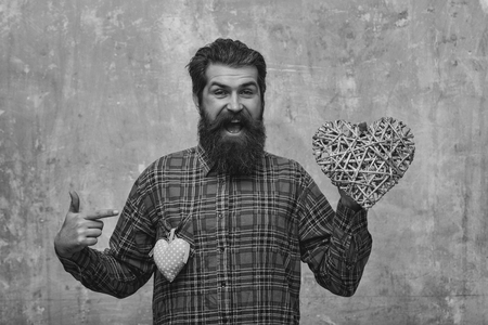 Man in love. Bearded happy man, Caucasian hipster, with long beard and mustache in plaid shirt with two hearts, wicker and rosy textile, love gifts for valentines day, on beige grunge wall background 版權商用圖片