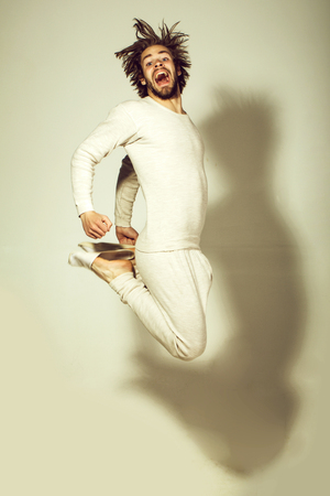 Happy man in pajamas. jumping happy man in morning with disheveled and uncombed long hair with beard on face in white underwear on grey background, energy and wake up, everyday life, morning exercise Stock Photo