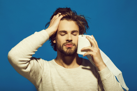 Advertising of toilet paper. man with closed eyes and sleepy face hold toilet paper in underwear on blue background Stock Photo