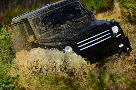 Off road vehicle or SUV crossing puddle with dirt splash. Competition, energy and motorsport concept Car racing in autumn forest. Auto racing on fall nature background Stock Photo