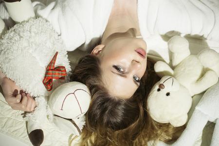 Pretty young woman lying on the floor with a teddy bear. 版權商用圖片
