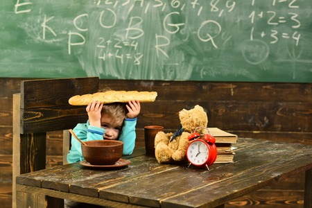 Break time. Little boy relax during school break. Child have lunch break at table in class. Take a break. Have a healthy snack at hand