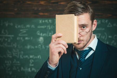 You should remember. Teacher formal wear and glasses looks smart, chalkboard background. Man unshaven holds book in front of face. Teacher insists on need to memorize information. Education concept