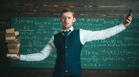 Man teacher balancing in hands pile of books and smartphone as analog and digital information storages. Teacher formal wear, chalkboard background. Smartphone smarter choice. Modern against outdated