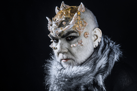 Stern demon with pale white skin tinted with gold. Evil creature controlling snow and frost, winter god. Monster with thorns on face wearing fur collar isolated on black background