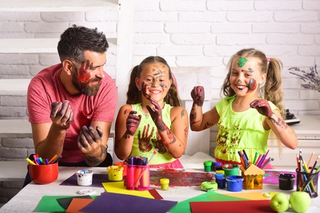 Girls and man with painted hands and faces