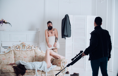 Husband arrived home to see wife cheat with lover. Aggressive man with gun to shoot couple in love. Hipster shocked to see gunman in bedroom. Cheating, jealousy and violence. Love triangle concept. 스톡 콘텐츠