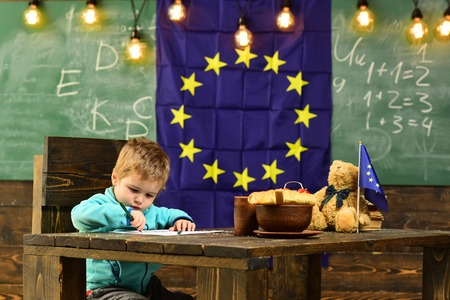 School break. Little boy drawing at table during school break. Child enjoy school break. School break in classroom with eu flag on chalkboard. I draw pictures all day Imagens
