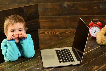 Future concept. Future Einstein with laptop on table. Little boy study computer technology for future life. A bright future begins here