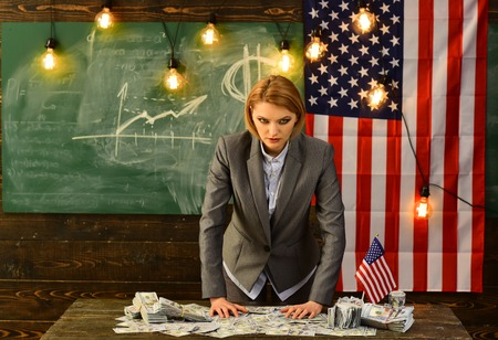 Serious woman dressed in suits with an American flag holding a bunch of dollar