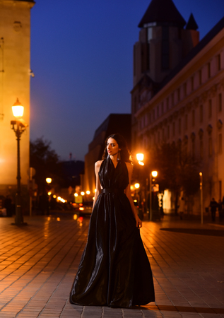 Luxury woman in evening dress at night city going to prom party Sexy girl in elegant dress. Fashion and beauty of business lady. Girl with glamour makeup. Night city with princess in celebrity style Stock Photo