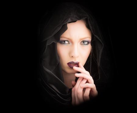 Sexy vrouw in zwarte kap. vrouw met modieuze make-up. Stockfoto