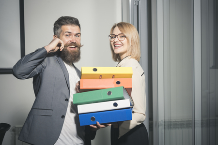 Office manager help woman colleague to carry binders with documents. Office romance and flirt concept