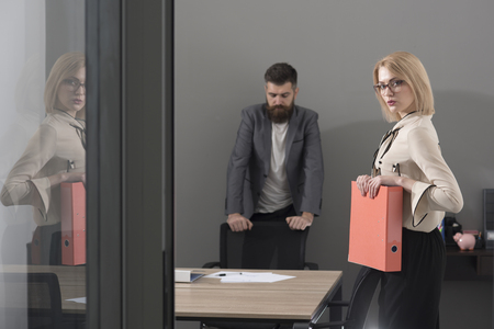 Confident and successful colleagues at work. Paperwork before deal. Woman and bearded man in office background. Business woman hold file folders. Contract with best conditions