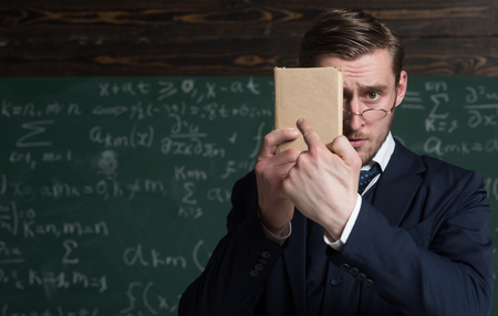 You should better learn it. Teacher formal wear and glasses looks smart, chalkboard background. Man unshaven holds book in front of face. Teacher insists on need learn information. Education concept Reklamní fotografie