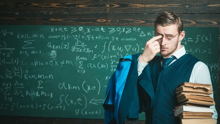Teacher formal wear and glasses looks smart, chalkboard background. Man in end of lesson takes off eyeglasses. Did you get it Chalkboard full of math formulas. Teacher finished explanation