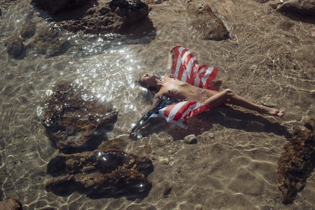 Sensual nude attractive girl on pensive face with usa flag on sunny day. Sexy naked lady lays in water near stone or reef in sea. Woman enjoy sun and suntanning. Vacation and freedom concept Stockfoto