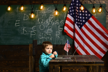 School kid at lesson in 4th of july. E-learning or online courses at home schooling. Patriotism and freedom. Little boy with laptop for business at American flag. Happy independence day of the usa
