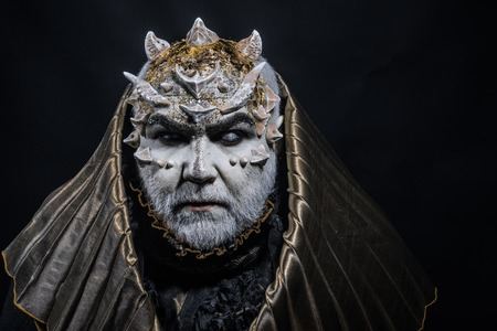Man with thorns or warts, face covered with glitters. Demon with golden hood on black background. Senior man with white beard dressed like monster. Fantasy concept. Alien, demon, sorcerer makeup.