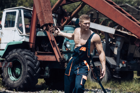 Power concept. Power man pull tractor with crane. Power lifter at construction site. Feel the power Stock Photo