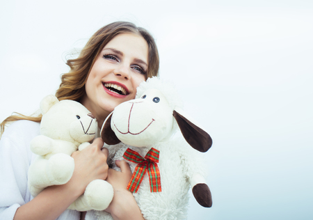Best present from him. Happy woman hold toys. Young woman smile with soft toys. Beauty girl with makeup on smiling face. Holidays celebration and birthday gifts, copy space