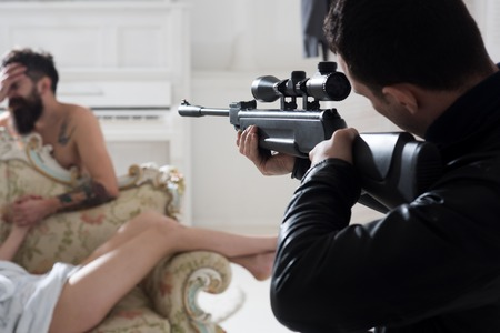 Man holding gun stand looking at couple with angry and jealous