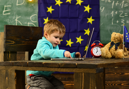 Innovation and technology. Little child use laptop computer in classroom with eu flag, innovation. Innovation in elementary school. Extending your reach with innovation
