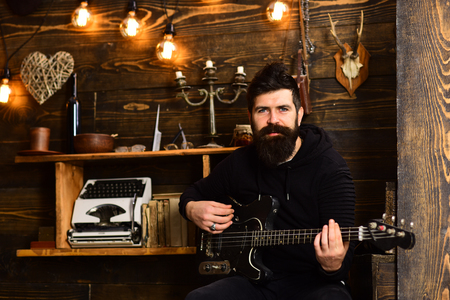 Man bearded musician enjoy evening with bass guitar, wooden background. Soul music. Man with beard holds black electric guitar. Guy in cozy warm atmosphere play relaxing soul music 写真素材