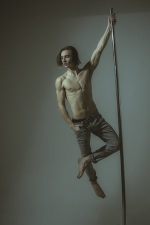 man dancing at pole in a fitness studio - Ballet dancer working out - Pole dancer stretching. Banco de Imagens - 104539911