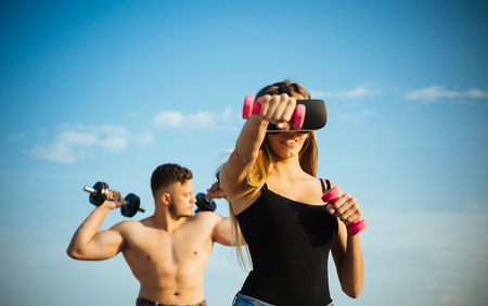 Virtual vision glasses. Woman use virtual simulator for fitness training. Virtual headset and gym equipment. In my virtual world Stock Photo