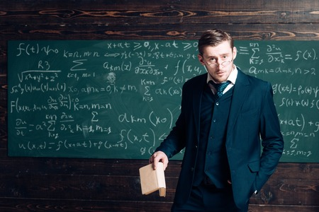 Exacting teacher. Teacher formal wear and glasses looks smart, chalkboard background. Man with high expectations looks unsatisfied with students knowledge. Professor exacting and strict holds book