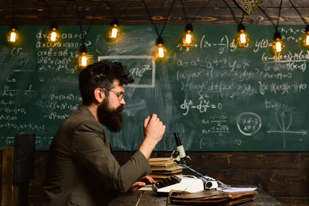 Copywriter blogger and journalist. Hipster man with beard and glasses type on typewriter creating content, writing article for blog