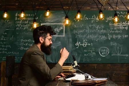 Copywriter blogger e giornalista. L'uomo hipster con barba e occhiali digita sulla macchina da scrivere creando contenuti, scrivendo articoli per blog