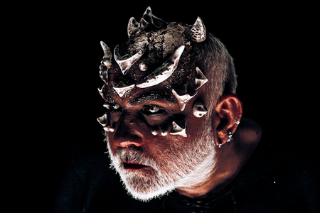 Monster with thorns and red dragon skin. Stern demon face with evil look isolated on black background. Man with fancy make-up, Halloween concept Stock Photo