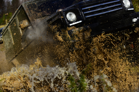 Competition, energy and motorsport concept. Car racing with dirty road. Off road vehicle or SUV crossing puddle with dirty water and mud splash, close up. 版權商用圖片