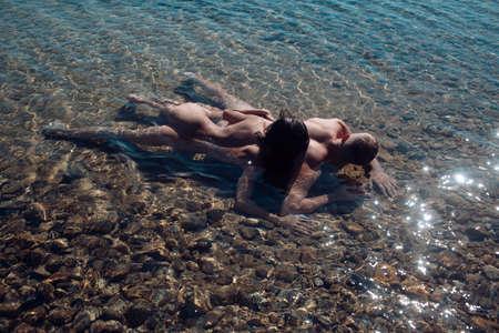 Hombre y mujer sexy tienen juegos. Pareja enamorada del cuerpo se relaja en la playa. Familia y día de San Valentín. Vacaciones de verano y vacaciones de viaje paradisíacas. Amor relaciones de pareja en agua de mar.