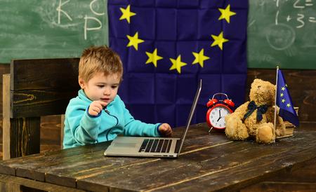School time. School boy use laptop in classroom with eu flag. Little boy study computer in elementary school. I got school spirit