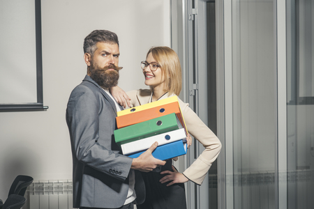 Colleagues hold folders with business documents. Colleagues work together in office, paperwork