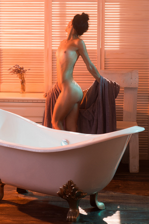 Well-groomed sexy woman after bath with a gown on bathroom background.