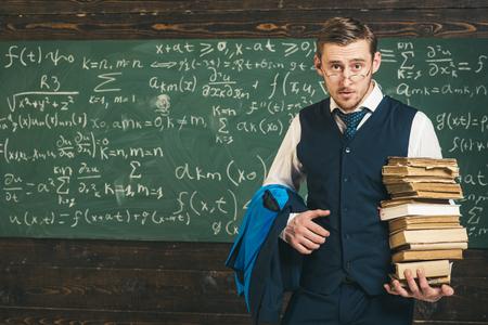 Check homework. Teacher formal wear and glasses looks smart, chalkboard background. Chalkboard full of math formulas. Man in end of lesson checking homework. Teacher finished explanation Stok Fotoğraf