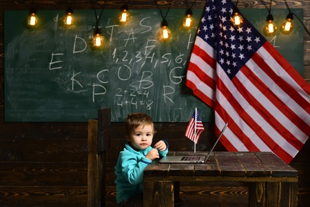 School kid at lesson in 4th of july. Little boy with laptop for business at American flag. E-learning or online courses at home schooling. Patriotism and freedom. Happy independence day of the usa Stock fotó