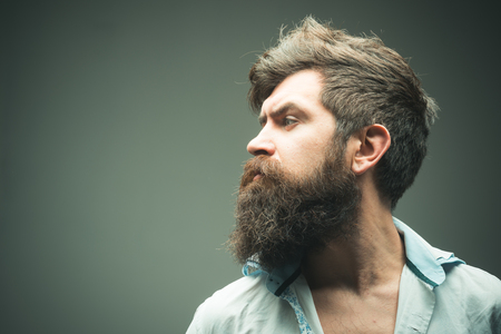 Man brutal bearded hipster side view, copy space. How grow great beard. Ways optimize facial hair. Beard grooming has never been so easy. Beard care tricks will keep facial hair looking resplendent.