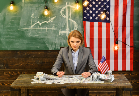 Attractive woman dressed in suit with an American flag hold dollar money. green background