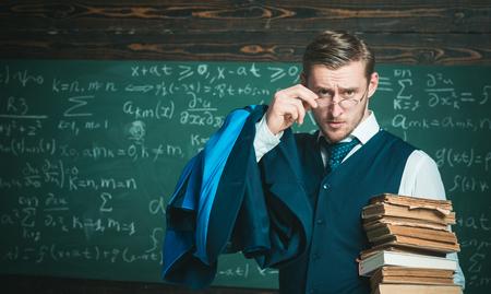 Check homework. Teacher formal wear and glasses looks smart, chalkboard background. Teacher finished explanation. Chalkboard full of math formulas. Man in end of lesson checking homework